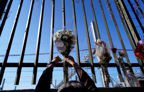 A relative of the Madrid train attacks victim, places flowers outside the Atocha station on the 15th anniversary of the attacks in Madrid (by REUTERS/Juan Medina)