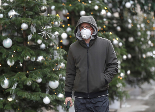 A man wearing a face mask walks past festively decorated Christmas trees (by REUTERS/Peter Nicholls)