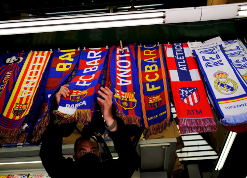 A stall selling scarves of FC Barcelona, Atletico Madrid, and Real Madrid (image from REUTERS/Nacho Doce)