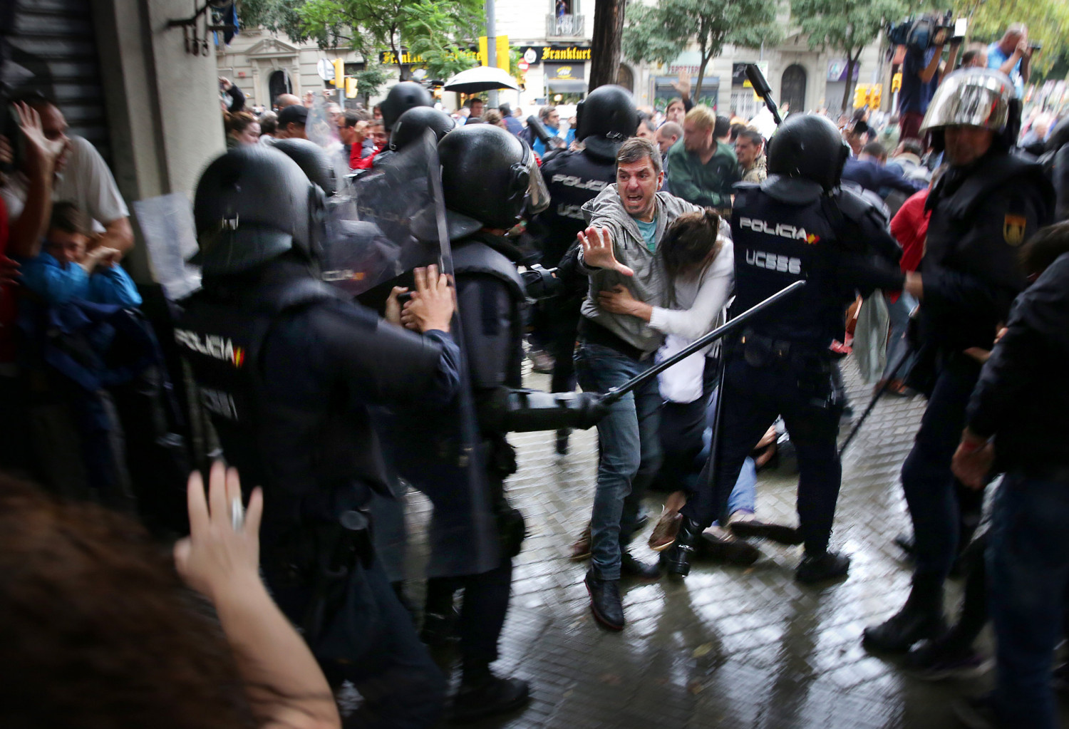 A man shields a woman from the police in Barcelona outside of an independence referendum polling station (by Jordi Play)