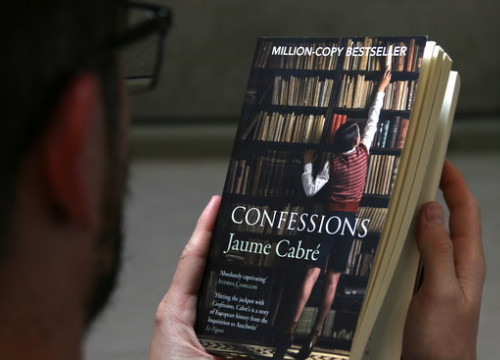 A reader holds an English version of Confessions on January 4 by Cabré (by Violeta Gumà)