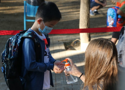 A student using hand sanitizer at a Barcelona school (by Miquel Codolar)