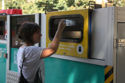 A woman recycling a plastic bottle in Barcelona's Bon Pastor neighborhood (by Ariadna Coma)