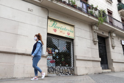 A woman walks past a closed florist on April 23 in Barcelona (by Mar Vila)