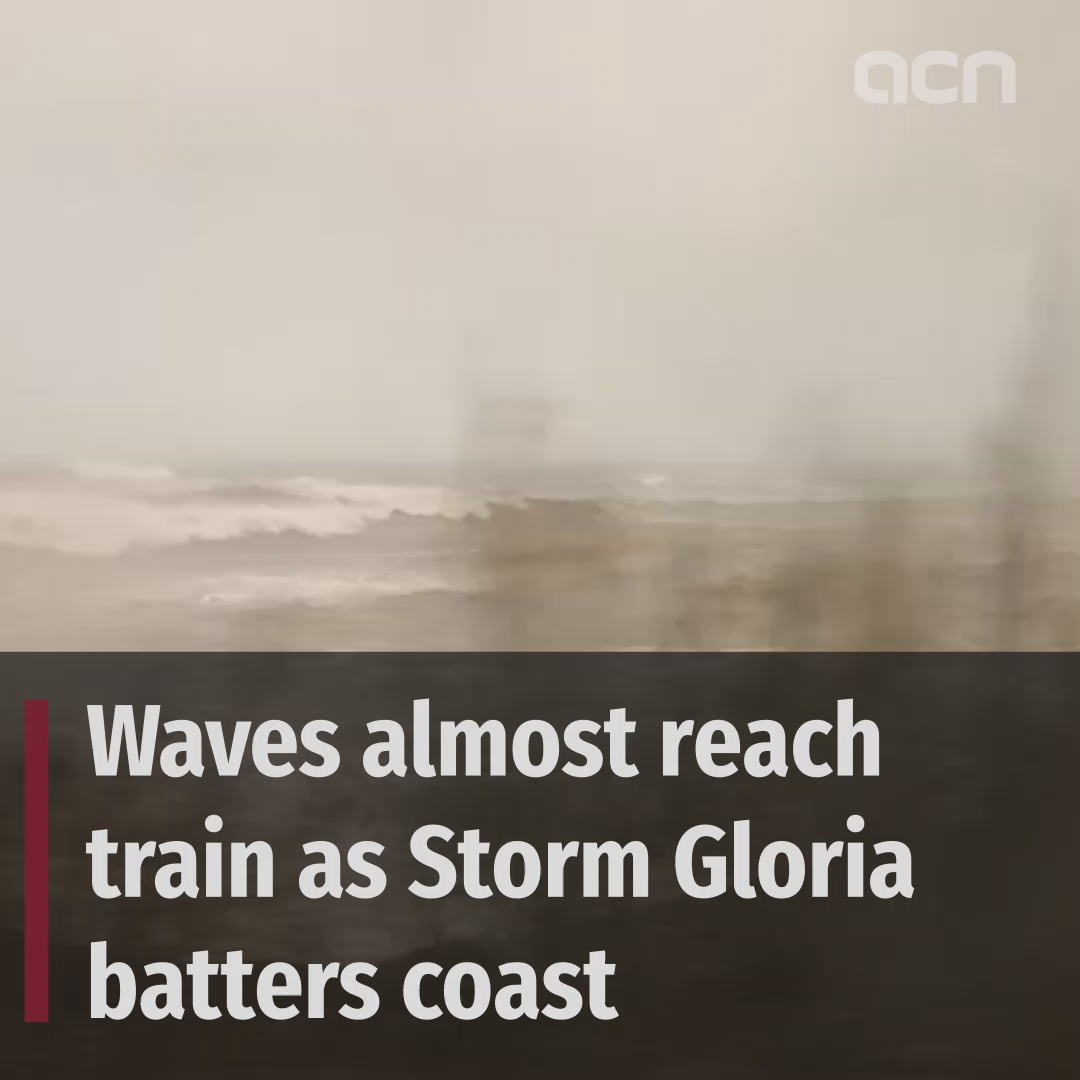 Waves nearly reach train as Storm Gloria continues to batter coast