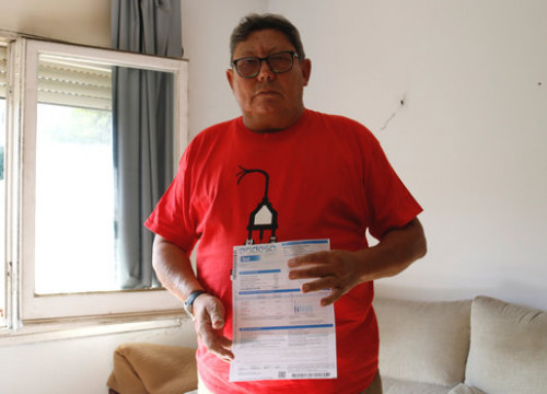 José Luis Jacas holds up one of his unpaid bills (Blanca Blay/ACN)