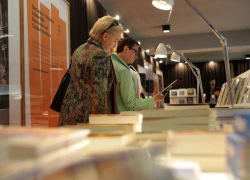 Women looking at some Catalan books at Institut Ramon Llull's stand at Warsaw Book Fair (by ACN)