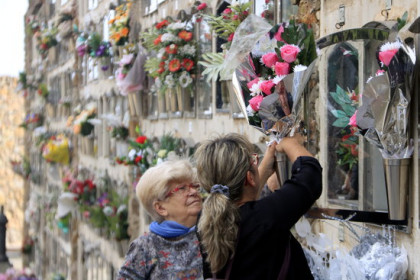 Two women place flowers in front of a family member's niche at Barcelona's Montjuïc cemetery on All Saints' Day (by Laura Fíguls)