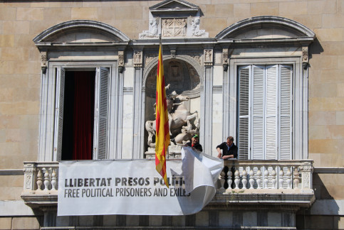 Workers take down a sign with a yellow ribbon on it on the Catalan government HQ's façade on March 22, 2019 (Miquel Codolar/ACN)