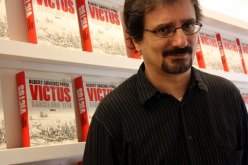 Albert Sánchez Piñol posing in front of a few copies of 'Victus' in 2013 (by ACN)