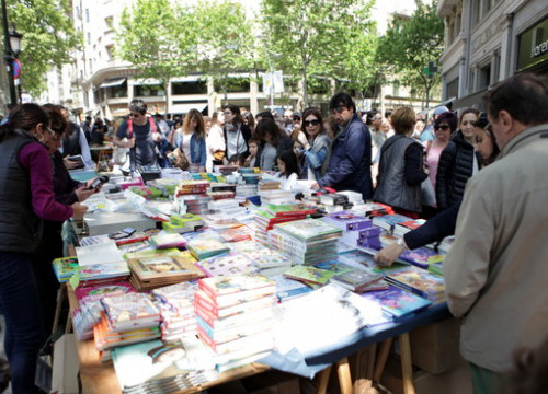 Readers trying to find a book in a stall in Barcelona during Sant Jordi (by ACN)