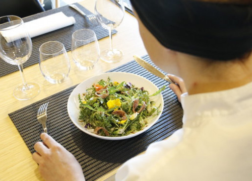A customer in a restaurant about to eat a chicory salad (by Ferran Queralt)