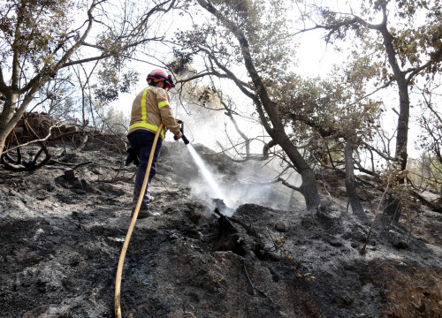 A firefighter putting out the fire near the Catalan village of Artés