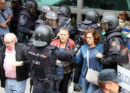 Spanish police officers circle two women outside a polling station on October 1 (by ACN)