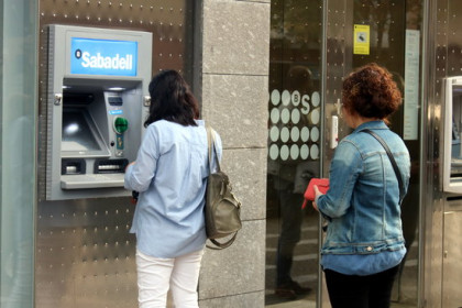 People queue to withdraw money from a Banc Sabadell ATM (by Xavier Pi)