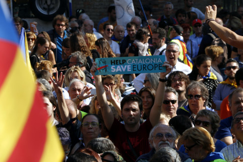 "Demonstrator holding a sign that reads ""Help Catalonia. Save Europe! (by Laura Busquets)"