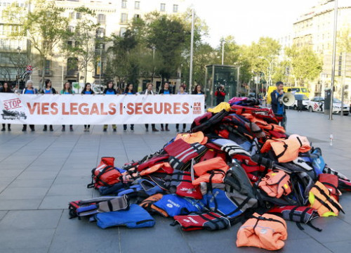 Stop Mare Mortum activists in central Barcelona with pile of life jackets (by ACN)
