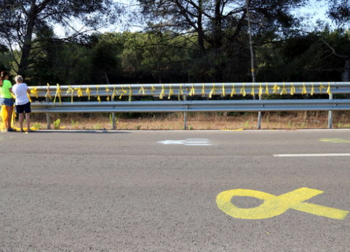 Two people placing yellow signs on a road leading to a prison where a political leader is incarcerated (by Núria Torres)