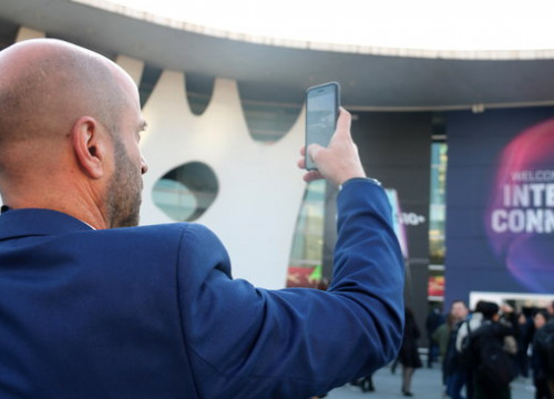 A man takes a photo at the entrance to MWC 2019 (by Laura Pous)