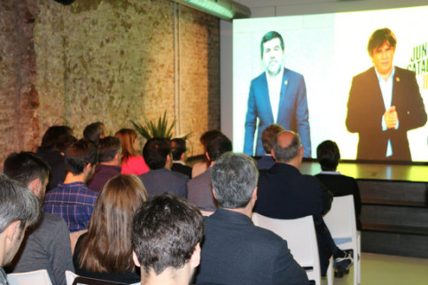 Image of a Junts per Catalunya event with former president Puigdemont and jailed leader Jordi Sànchez attending via videolink on April 22 (by Bernat Vilaró)