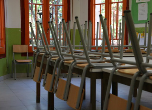 A school classroom with chairs stacked onto the tables (by Elisenda Rosanas)