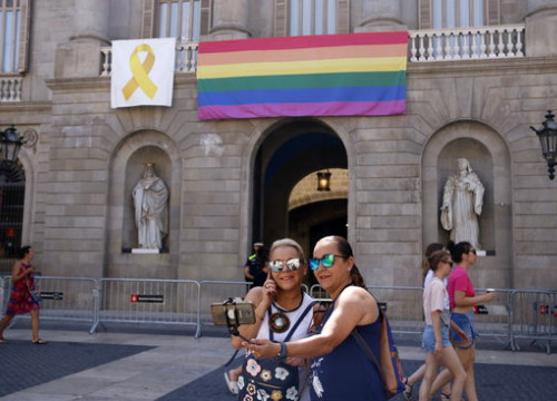 Two people take a selfie with an LGBTQI flag hanging from the Barcelona City Council building (by Sílvia Jardí)