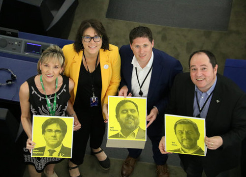 MEPs Martina Anderson, Matt Carthy, Diana Riba, and Pernando Barrena hold up photos of Carles Puigdemont, Oriol Junqueras, and Toni Comín in the European Parliament plenary session on Jul 2, 2019 (by Natàlia Segura)