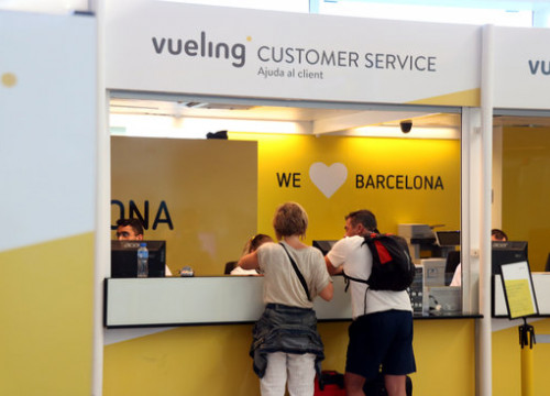 Passengers visit the Vueling customer service desk in the Barcelona airport (by Miquel Codolar)
