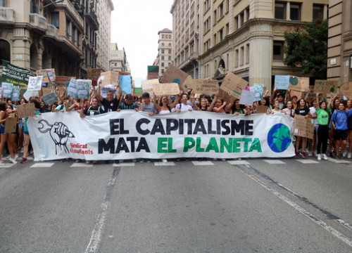 Image of a demonstration for climate with a banner reading 'Capitalism kills the planet,' on September 27, 2019 (by Gerard Comas)