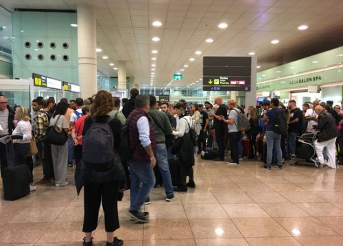 Passengers affected by protests at Barcelona airport queue up for information (by Xavi Toscano)