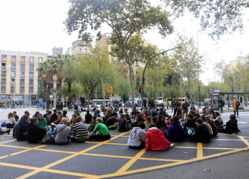 Students block a road on Plaça Universitat in front of the historic University of Barcelona building (by Laura Fíguls)