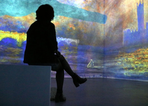 A woman sits in front of one of the immersive Monet exhibitions at the Ideal arts center in Poblenou, Barcelona (by Pilar Tomás)