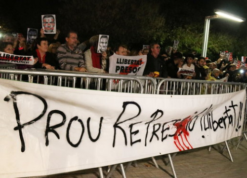 "Protesters stand behind a banner that reads ""Enough repression, freedom!"" (by Norma Vidal)"