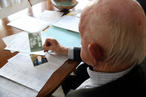 Josep Sabatés looking at a photograph of his father and his siblings, one of the few records he has of his uncle (by Estefania Escolà)