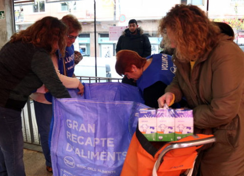 A shopper gives donations to volunteers in a supermarket during the 2019 'Gran Recapte' food drive (by Elisenda Rosanas)