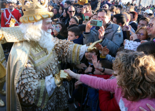 Melchior, one of the three magic kings, greets parade-goers on the night before King's Day (by Miquel Codolar)