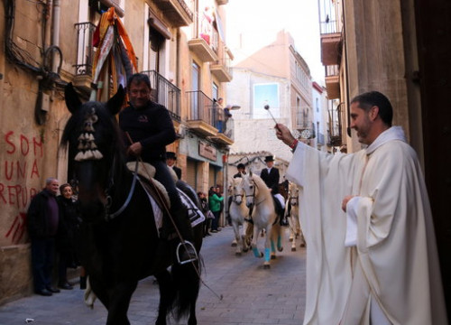A man riding a horse being blessed by a priest from the church of Saint Anthony in Valls during the Tres Tombs festival on January 12, 2020 (by Mar Rovira)