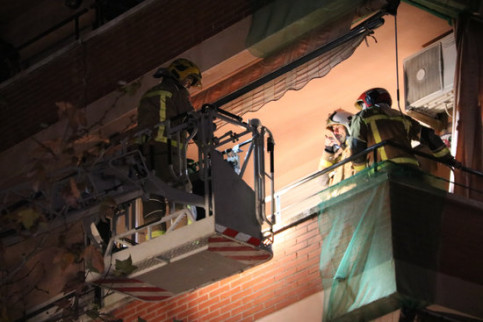Firefighters assist one of the neighbors in the building hit by the piece of metal thrown off from the explosion at the chemical plant in southern Catalonia (by Núria Torres)