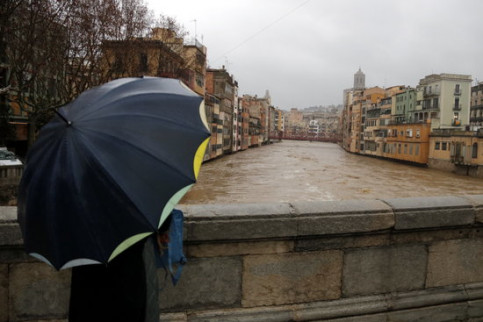 A man holding an umbrella stops to take a picture of the elevated water in the river Onyar in Girona (by Marina López)