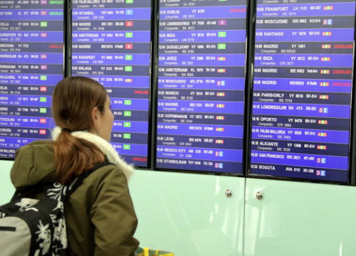 A passenger looks at the flight information screens in Barcelona airport, after a spate of flights were cancelled on the first day of the state of alarm declared for the covid-19 coronavirus crisis (by Àlex Recolons)