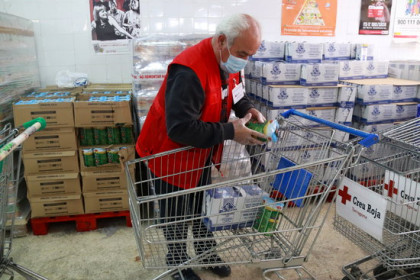 A volunteer for the Red Cross in Tarragona fills up a shopping cart for a person in a vulnerable situation (by Eloi Tost)