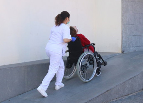 A home care worker takes care of an elderly person in a wheelchair (by Eloi Tost)