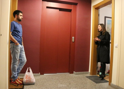 Two neighbours chatting in an apartment building in Sabadell where the community have started an initiative to buy shopping for vulnerable neighbours (by Norma Vidal)