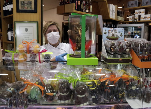 A baker wearing a face mask during the coronavirus crisis stands behind an assortment of Easter 'mones de Pasqua' cakes (by Marina López)
