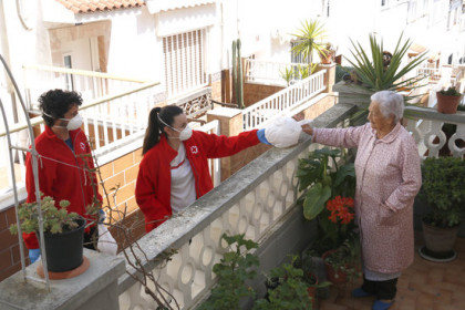 Two Red Cross volunteers deliver food to a woman unable to leave her home in Blanes, April 9, 2020 (by Aleix Freixas)