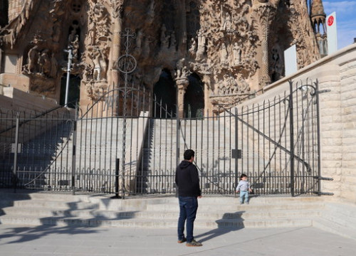 A parent and child out for a walk in front of the Sagrada Familia after confinement restrictions on children leaving the house were lifted on April 26, 2020 (by Mar Vila)