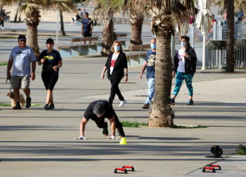 A man exercises as others go for strolles in Badalona on the first day after lockdown restrictions were lifted for the whole population (by Àlex Recolons)