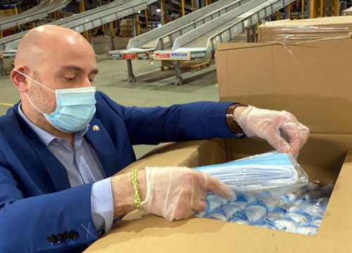 A Spanish government worker managed boxes of face masks before they were sent to regions (image by Moncloa)