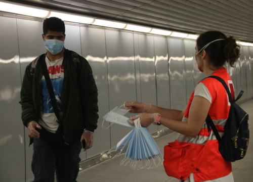 A Red Cross volunteer gives out Spanish government masks on Barcelona's underground on May 4, 2020 (by Albert Cadanet)