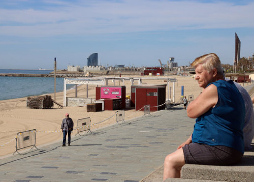 People looking over Bogatell beach in Barcelona, closed during the Covid-19 coronavirus crisis (by Miquel Codolar)